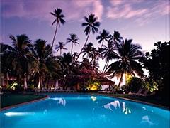 Hotel Tropical. piscina y cocoteros al atardecer